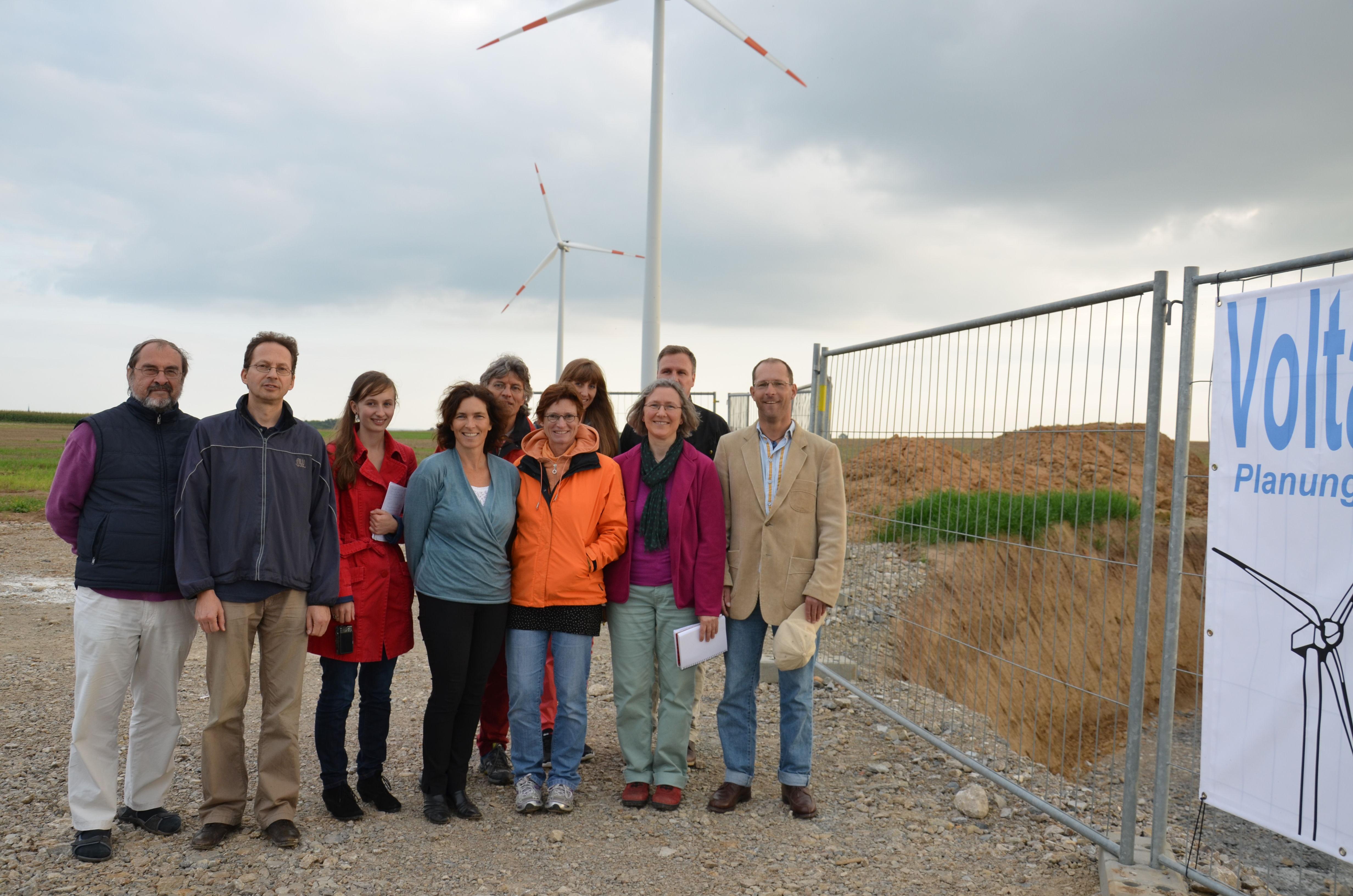 Die Grüne Besuchergruppe vor zwei Windrädern der Volta GmbH