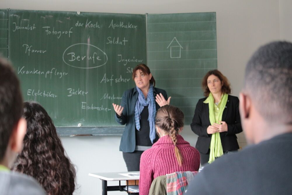 Kerstin Celina und Ekin Deligöz vor der Tafel im Klassenzimmer der Schule.