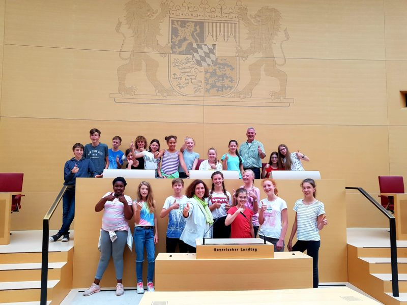 Das Foto zeigt die Gruppe zusammen mit der Abgeordneten Kerstin Celina (vorne), der Jugendzentrumsleiterin Ruth Braun und dem 1. Bürgermeister der Gemeinde Rottendorf Roland Schmitt (beide in der hinteren Reihe) beim Rednerpult und den Präsidiumssitzen im Plenarsaal des Bayerischen Landtags. Die Fotorechte liegen bei Kerstin Celina.